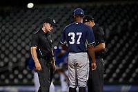 Umpires Austin Nelson and Michael Corbett examine the glove of Edwuin Bencomo (37) during an Arizona League game between the AZL Padres 1 and the AZL Cubs 1 on July 5, 2019 at Sloan Park in Mesa, Arizona. The AZL Cubs 1 defeated the AZL Padres 1 9-3. (Zachary Lucy/Four Seam Images)