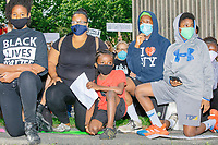"""People take a knee for 8 minutes and 46 seconds outside the Boston Police Department Headquarters during the """"Peaceful Children's March: Be the Change"""" demonstration in support of Black Lives Matter in Boston, Massachusetts, on Sun., June 7, 2020. The children's march was organized by siblings Naheem, 7, (red shirt) and Anaysha Benalfew, 10 (Black Lives Matter shirt). The demonstration is part of a weeks-long nationwide response to the killing of George Floyd by Minneapolis police on May 25, 2020. The march started near the Nubian Square bus depot and continued to the nearby Boston Police Department headquarters, where marchers knelt for 8 minutes and 46 seconds, the time that police officers knelt on George Floyd's neck during his killing. A number of children, mostly people of color, then spoke about how people should be treated equally and how they wished they didn't have to grow up fearful that a police officer would kill them or their loved ones."""