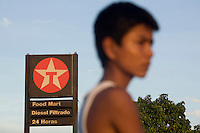 Darwin Quindigua, 15, stands in front of a Texaco sign at a petrol station in Lago Agrio. A class action lawsuit was brought against US multinational oil giant Texaco (acquired by Chevron in 2001) by more than 30,000 Ecuadorians. The case has been in the Ecuadorian courts since 2003 and relates to the dumping of billions of gallons of toxic materials into unlined pits and Amazonian rivers. In February 2011 the court ruled that Chevron should pay a fine totalling 9.5 billion USD. However, Chevron has stated that the ruling is 'illegitimate and unenforceable' and has started numerous counter proceedings in US courts. There is some doubt as to whether it will be possible to force Texaco to pay the fine.