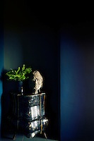 A fern in a vase and a stone bust are placed on a blue chest of drawers with a distressed paint finish, which stands in a recess.