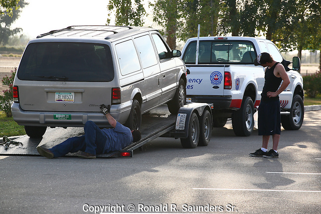 TOW TRUCK PREPARES TO TRANSPORT VEHICLE WHILE DRIVER LOOKS ON (1)