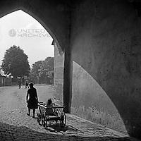 Ein Mädchen zieht ein  Kleinkind in einem Handkarren durch einen Torbogen in der Altstadt von Dinkelsbühl, Deutschland 1930er Jahre. A girl pulling a toddler in a handcart through an arch at the old city of Dinkelsbuehl, Germany 1930s.