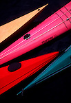 Four sea kayak bows, one of fiberglass, one of wood, one of roto-molded plastic and one of fabric and aluminum frame,.