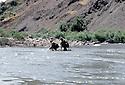 Irak 1985  Dans les zones libérées, région de Lolan, deux peshmergas traversant une riviere sur un radeau   Iraq 1985 In liberated areas, Lolan district, two peshmergas crossing a river on a raft