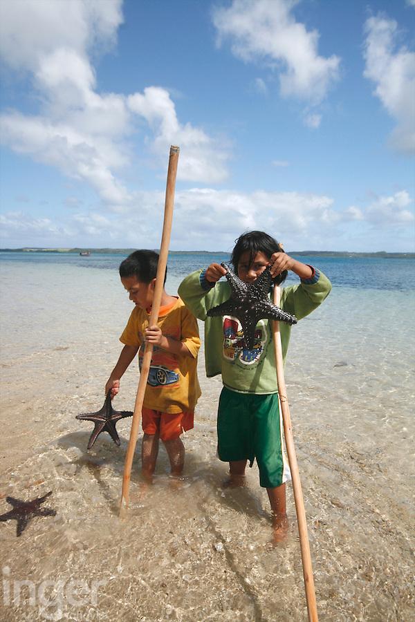 Children playing with starfish in Tonga