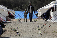 Pictured: A man and his son walk by rows of tents Friday 26 February 2016<br />Re: Hundreds of refugees have been given temporary shelter at the Stefanakis Army Camp in the Schisto area of Athens, Greece.