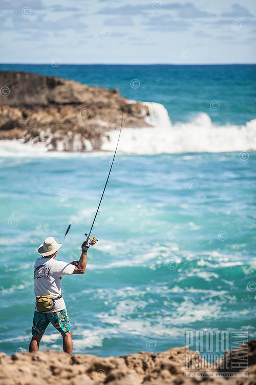 A fisherman casts his fishing line into the Pacific Ocean off La'ie Point on O'ahu.