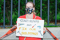 """A demonstrator holds a sign reading """"Start Remote and Fix Our Buildings"""" as people gathered outside the Massachusetts State House for a protest organized by the Massachusetts Teachers Association against current school reopening plans during the ongoing Coronavirus (COVID-19) global pandemic in Boston, Massachusetts, on Wed., Aug. 19, 2020. The teachers' union, alongside two other Massachusetts teachers' unions, organized the event as part of a mass day of action demanding that the school year starts with remote learning and switch to in-person learning only when health and safety standards can be guaranteed."""