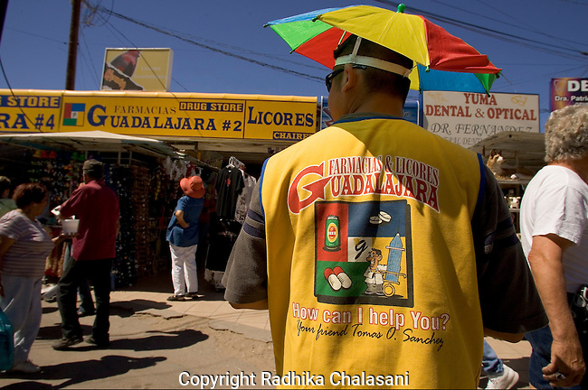 ALGODONES, MEXICO-MARCH 22: A tout looks to encourage American visitors to enter the Guadalahara Pharmacy one block from the U.S. border March 22, 2005 in Algodones. The Pharmacy is one of more than a dozen businesses in town selling medications to foreign visitors and prices one third to one half of those in the U.S. ©Radhika Chalasani