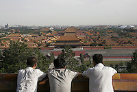 Visitors look at the Forbidden City from the Jinshan Hill in Beijing, China..01 Jul 2005