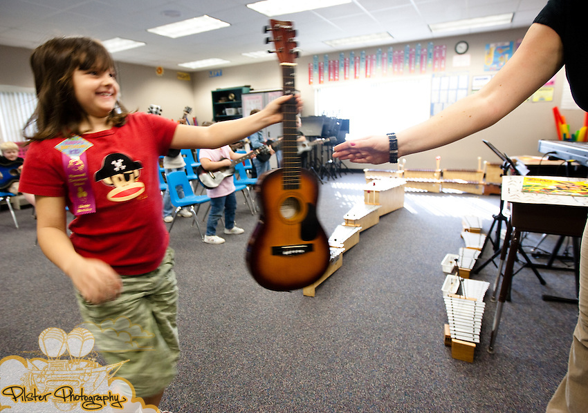 Dayla Ware, left hands Darci Halloran, a music teacher, her guitar after her 2nd grade class finished their lesson on Thursday, December 17, 2009, at Pinewood Elementary School in Mims, Florida. Halloran was awarded a grant to purchase guitars for her music students. (Chad Pilster, http://www.PilsterPhotography.com)