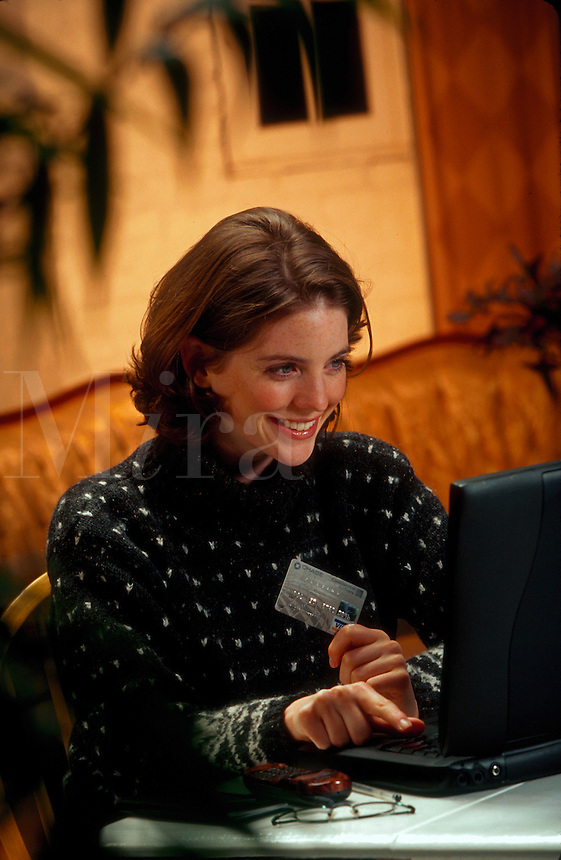 A smiling young woman making a purchase with a credit card as she shops online from a laptop computer.