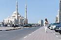 Evelina Farinacci, sassarese a dispetto del cognome, vive e  lavora negli Emirati Arabi da circa dieci anni. Per 5 anni ha lavorato per la Camera di Commercio Italiana negli EAU. Qui è ritratta mentre cammina lungo la Corniche di Sharjah. Alla sua sinistra la Nur Masjid, la Moschea della Luce.