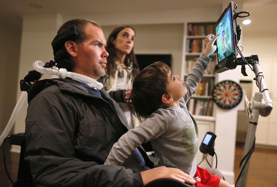 In this Monday, Jan. 18, 2016 photo, former New Orleans Saints NFL football player Steve Gleason watches as his four-year-old son, Rivers, plays on his father's tablet as his wife, Michel, answers a question during an interview in New Orleans. (AP Photo/Jonathan Bachman)