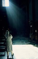 Nun praying inside St. Peter's Basilica, Rome, Italy.
