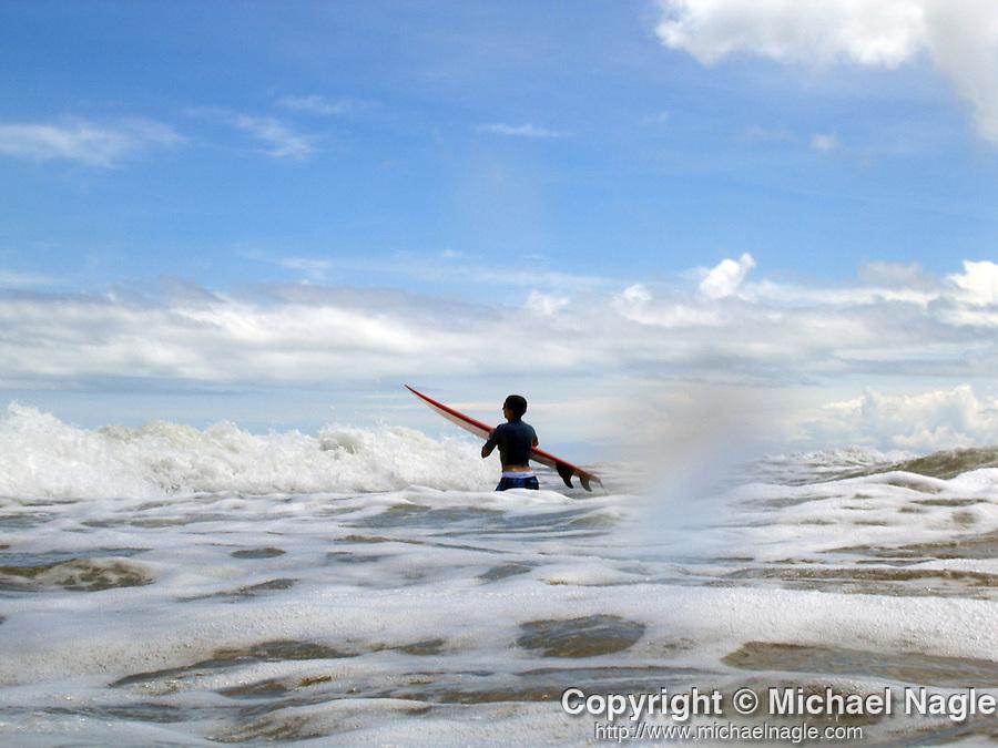 A surfer wades through waves at Playa Carmen in Mal Pais, Costa Rica.  (PHOTOGRAPH BY MICHAEL NAGLE)