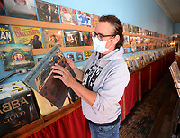 Wade Ogle, owner of Block Street Records, sorts through records Thursday, Oct. 7, 2021, at the longtime store in Fayetteville. Sales tax revenue for the city of Fayetteville topped $2.3 million in September. Visit nwaonline.com/211008Daily/ for today's photo gallery.<br /> (NWA Democrat-Gazette/Andy Shupe)