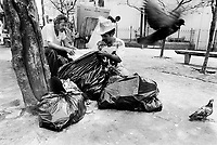 """Brazil. Sao Paulo state. Sao Paulo. Jose is 38 years old. He is a poor man who lives in the street. He wears a hat and is checking with a friend the contents of a plastic bag full of garbage. The """"catadores"""" are men who collect paper, plastics, metals, bottles ... in order to sell these items as recycled materials and make a living. Waste collector. A pigeon is flying away. © 1994 Didier Ruef .."""