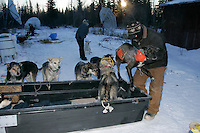 Wednesday March 7, 2007   Nikolai resident and volunteer John Runkle loads a dropped dog into a sled to haul them to the runway where a Penair plane waits to take them back to Anchorage.