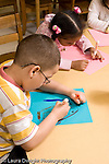 Preschool 4-5 year olds boy wearing glasses drawing with marker girl drawing behind him vertical