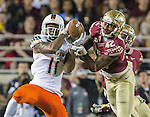 Florida State defensive back Lamarcus Brutus makes a break for an interception but misses and Miami's wide receiver Rashawn Scott making the reception and scampering 58 yards for the touchdown in the second quarter of an NCAA college football game against Miami in Tallahassee, Fla., Saturday, Oct. 10, 2015.   The Florida State Seminoles defeated the Miami Hurricanes 29-24.