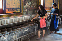 Bangkok, Thailand.  Wat Pho Temple.  Worshipers Placing Coins in Pots while Seeking Blessings or Good Fortune.