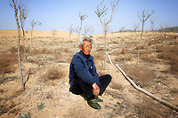 A worker takes a break whilst waiting for water to be pumped onto dry farmland in Hebei Province, China.  Desertification is the process by which fertile land becomes desert, typically as a result of drought, deforestation, or inappropriate agriculture. 41 % of China's landmass in classified as arid or desert. Inappropriate farming methods and over cultivation have contributed to the spreading of deserts in China in recent years.