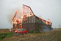 Farmer runs for help as his barn burns from a lightning strike.