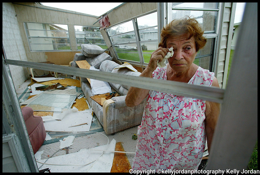 Jelena Atanackovic wipes tears away as she looks at the damage to her Wilbur-By-The-Sea, Florida, home after FEMA representatives asked to survey her damage Thursday September 9, 2004.
