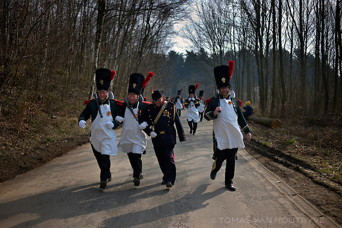 Men in 19th century historical Belgian uniforms participate in the St. Veroon procession in Tubize, Belgium on April 1 2013. Spectators to the procession give drinks to the passing marchers, and soon many of them are stagering drunk. The procession partially follows the exact border between Flanders and Wallonia.