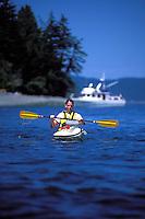 Male sea kayaker with waterproof camera case on deck.  Motor yacht visible in background. Cypress Island, San Juan Islands, Washington