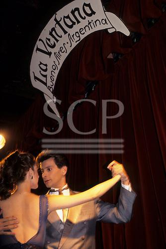 Buenos Aires, Argentina. Couple dancing the Tango below a sign 'La Ventana'.