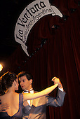Buenos Aires, Argentina. Couple dancing the Tango below a sign 'La Ventana'.