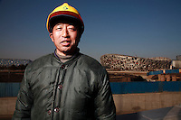 Wei Chaoyun, A migrant worker who has been working as manual labor on various projects at the National Stadium AKA the Bird's Nest for the past two years, is photographed near the stadium in Beijing, China. ©Qilai Shen/Sinopix