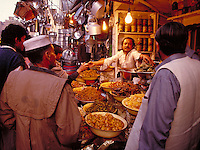In Pakistan, a man sells a variety of foods to shoppers in an open air market. occupations, trade, food, merchants, shopping, vendor. man selling food on street. Pakistan street food market.