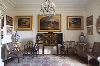Two Oriental horses flank a Japanese lacquered cabinet in this room, while more horse and dog paintings are arranged in symmetrical posees around the room