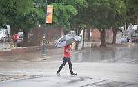 A pedestrian crosses Dickson St. Wednesday April 28, 2021 in Fayetteville during a rainstorm. The National Weather Service is calling for more rain Thursday then clear skies with high temperatures in the 70s this weekend. Visit nwaonline.com/210429Daily/ and nwadg.com/photo. (NWA Democrat-Gazette/J.T. Wampler)