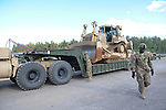 "American soldiers with the 15th Engineer Battalion help unload $28.5 million of equipment including a D7 Romeo on an 870 lowboy trailer for a two week-long NATO exercise at the Drawsko Pomorskie Training Area in Poland on June 10, 2015.  NATO is engaged in a multilateral training exercise ""Saber Strike,"" the first time Poland has hosted such war games, involving the militaries of Canada, Denmark, Germany, Poland, and the United States."