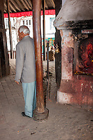 Nepal, Kathmandu.  Hindu Man Rubbing his Back against a Pole in the Kasthamandap Temple, built 11th Century.  March 2, 2009.  This temple was completely destroyed in the earthquake of April 2015.