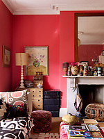A Victorian fireplace dominates one wall of the red-painted living room, its mantelpiece crowded with objects