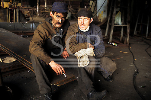 Gdansk, Poland. Two tired shipyard workers taking a cigarette break.