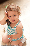 13 month old baby girl at home holding cellular telephone holding it to ear as if talking on the phone vertical
