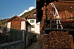 Barn with firewood neatly stacked and a sculpture on the balcony in Bondo, a Bregaglia Swiss Valley town, where the houses date back to the 16th century