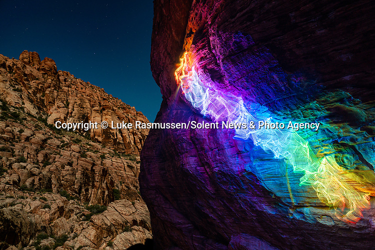 """Pictured:  A 30 second exposure at Cannabis Crag, Red Rock Canyon, Las Vegas, NV<br /> <br /> Bright bolts of colourful light snake their way across mountains and cliffs.  The striking images were created by a rock climber who wrapped LED lights around his body before capturing long exposure shots of his route.<br /> <br /> Luke Rasmussen took the photos in the deserts of Nevada, in the United States, and admits that his method of 'freezing time in a moment' is unusual.  The 28 year old photographer said: """"Wearing a sweater full of lights and climbing through the darkness of night is certainly a different experience than most climbers will get.  SEE OUR COPY FOR DETAILS.<br /> <br /> Please byline: Luke Rasmussen/Solent News<br /> <br /> © Luke Rasmussen/Solent News & Photo Agency<br /> UK +44 (0) 2380 458800"""