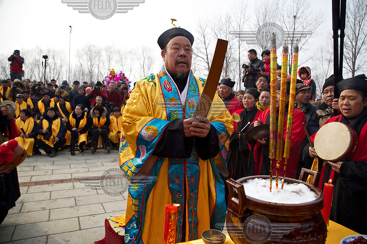 A Taoist priest blesses the Ma Jie folk festival. <br /> <br /> For centuries farmers in Henan have gathered during Chinese New Year in the region's wheat fields to listen to bards singing and recounting old tales. <br /> <br /> Now storytellers come from all over China to attend the annual festival where large crowds gather to watch the best performers.