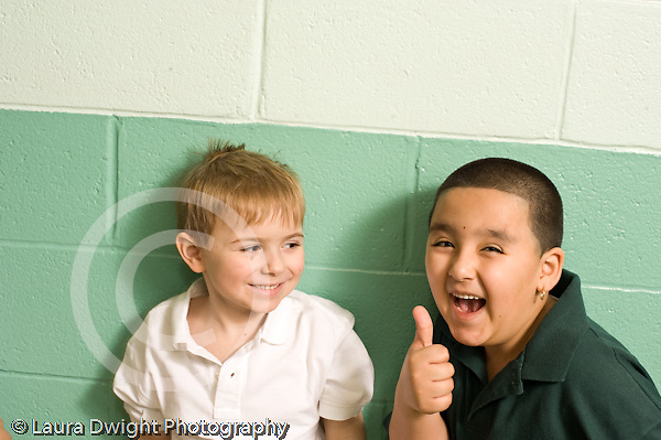 Elementary school Education Kindergarten two male students in corridor one clowning and laughing horizontal