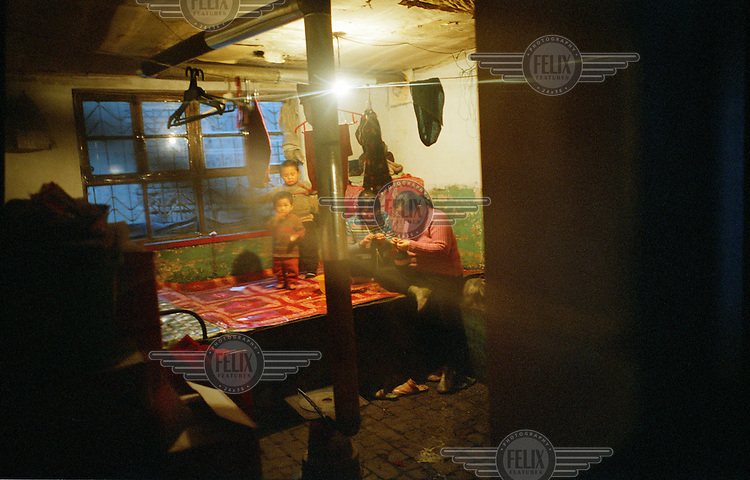 A family in the living quarters of their house. In the centre of the room is a typical stove which heats the home and is used for cooking.