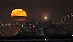 Thr May full moon rising over Alcatraz Island, San Francisco, CA as seen from Sausalito, CA.