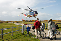 Family on bicycles viewing helicopter taking off from Tresco heliport.