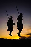 Two Masaai warriors silhouetted performing traditional jump / leap kopje at sunset. Ngorongoro Conservation Area / Serengeti National Park, Tanzania. March 2014.